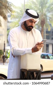 Arab Man Using Mobile Phone And Wearing UAE Tradational Dress  (  Internet Wi Fi Technology )