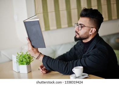 Arab man wear on black jeans jacket and eyeglasses sitting in cafe, read book and drink coffee. Stylish and fashionable arabian model guy.