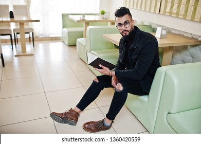 Arab man wear on black jeans jacket and eyeglasses sitting in cafe, read book. Stylish and fashionable arabian model guy.
