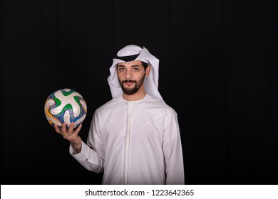 Arab man wearing kandora holding soccer ball isolated on black background.