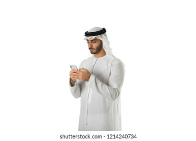 Arab man wearing Kandoura chatting or typing text message using cell phone isolated over white background