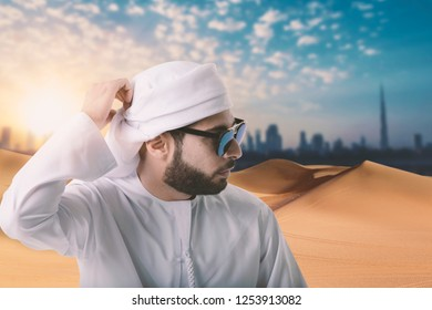 arab man wearing traditional clothes over desert and dubai city view, Travel concept