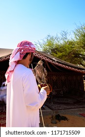 An Arab man, wearing white kandura and typical red checked United Arab Emirates head scarf, carrying his pet falcon in his arms at al qattara souk in Al Ain, United Arab Emirates-12th November,2016.