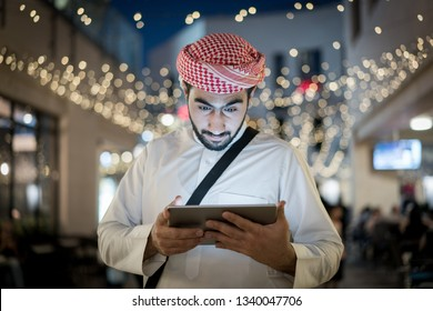 Arab men with tablet in city at night