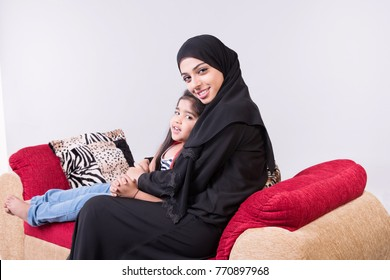 Arab mother with her child setting on sofa chair with white background