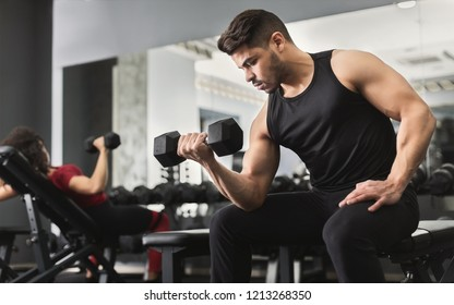 Arab muscular man doing biceps workouts with dumbbells in gym, copy space