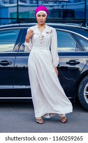 Arab Muslim business woman hijab with makeup standing in front of her luxury car on the street on a background of skyscrapers . The woman is dressed in a stylish abaya