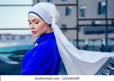 Arab Muslim business woman hijab with makeup standing on the street on a background of skyscrapers . The woman is dressed in a stylish abaya nikah