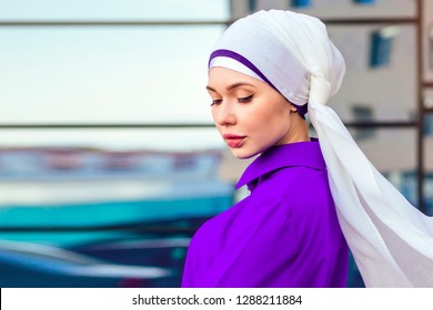Arab Muslim business woman hijab with makeup standing on the street on a background of skyscrapers . The woman is dressed in a stylish abaya nikah.world hijab day