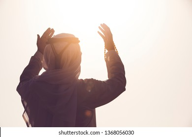 Arab Muslim man pray and doing Duaa under sunrise light, Islamic religion and Ramadan Kareem concept.