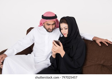 Arab muslim married couple using smart phone while sitting on sofa chair at home with white background