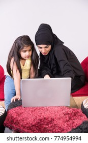 Arab muslim mother helping her child with homework with white background