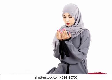 Arab Muslim woman praying on a praying carpet. Isolated on white background