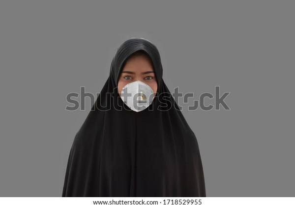 Arabische muslimische Frau mit Gesichtsmaske, um sich vor dem Corona-Virus zu schützen Isolated auf grauem Hintergrund.