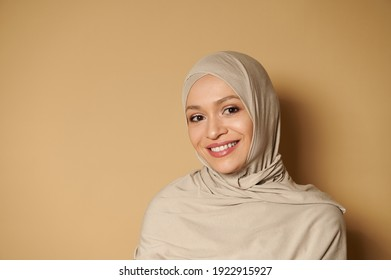 Arab muslim woman wearing hijab looking at camera while posing with a beautiful toothy smile on a beige background with copy space. Strict formal outfit and elegant appearance. Islamic fashion.