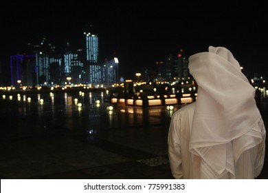 An Arab Qatari man wearing a white thobe or thwab (Arab garment) and white ghutra (or keffiyeh or headress) looking out to the evening or night skyline of Doha, Qatar