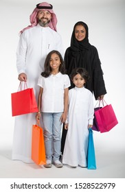 Arab Saudi family at the mall with colored shopping bags, on white isolated background, ready for cutout and design purposes.