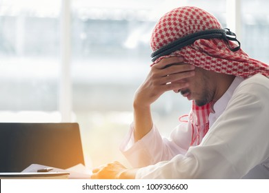 Arab saudi man working in a office, Arab businessman strain work hard, Concept of emotional distress, tired man with his hands on the his face at the table with a laptop in the office