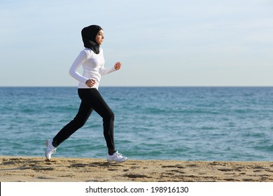 Arab saudi runner woman running on the beach with the sea and horizon in the background