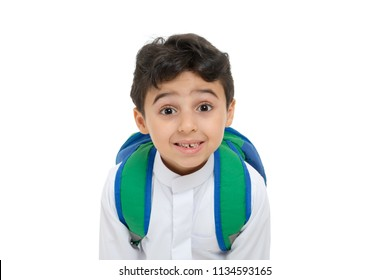 Arab school boy closeup on face with a smile and broken tooth, wearing white traditional Saudi Thobe, back pack and sneakers, raising his hands on white isolated background