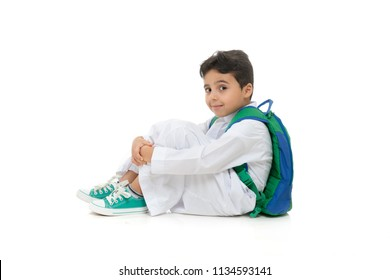 Arab school boy sitting on ground with a smile on his face, wearing white traditional Saudi Thobe, back pack and sneakers, raising his hands on white isolated background