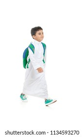 Arab school boy smiling and walking, wearing white traditional Saudi Thobe, back pack and sneakers, raising his hands on white isolated background