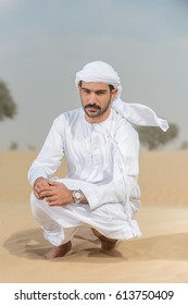 Arab sitting on the sand in the desert and looking in the camera