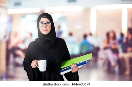 Arab student holding books and a cup in a university. Arabic education concept.