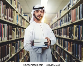 Arab student standing in library holding books on his arms. education concept.