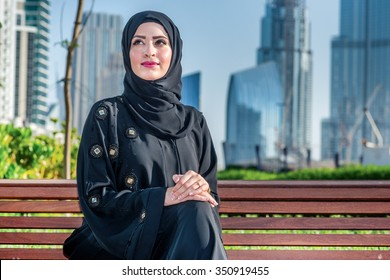 Arab success. Arab businesswomen in hijab sitting on the bench on the background of skyscrapers in Dubai while smiling to the side. The woman is dressed in a black abaya