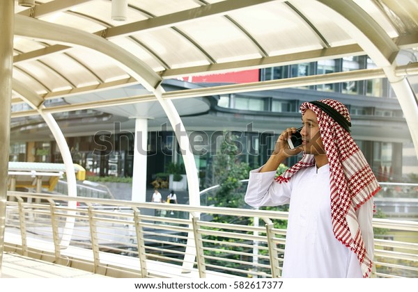 Arab is talking on the phone with background city.