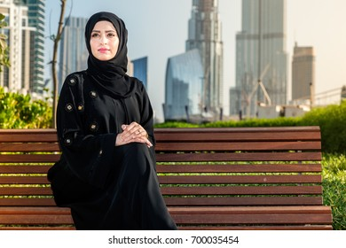 Arab woman in abaya is sitting on the bench and looking away.