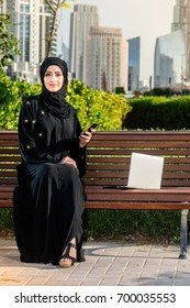 Arab woman in abaya sitting on the bench in the city park. Businesswman holding phone and looking in the laptop.
