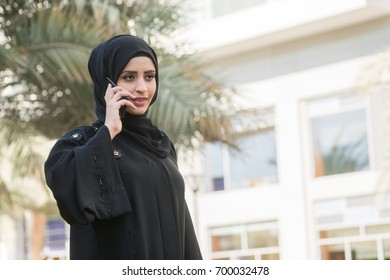 Arab woman in abaya talking by phone. Young muslim lady holding cell phone.