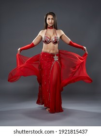 Arab woman belly dancer in red sparkling costume on gray background
