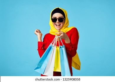 Arab woman in burqa with packages on a blue background shopping