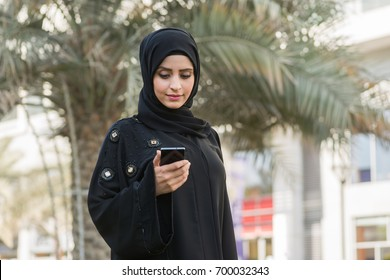 Arab woman dialing phone number using cell phone outside office.