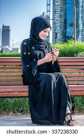 Arab woman got the message. Arab businesswomen in hijab holding of cell phone and read the message on the background of skyscrapers of Dubai. The woman is dressed in a black abaya