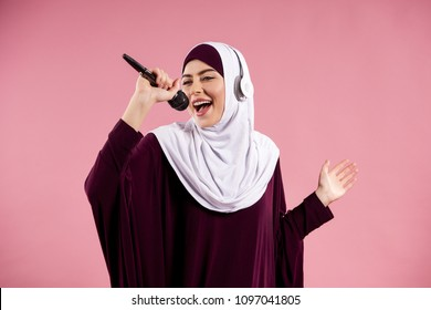 Arab woman in headphones sings karaoke. Isolated on pink background. Studio portrait.
