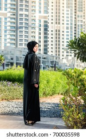 Arab woman in hijab standing in the city Park and looking back