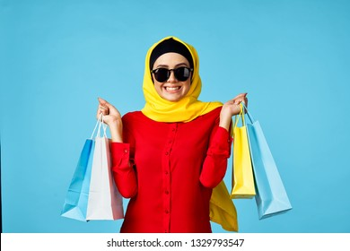 Arab woman joyful with packages on a blue background