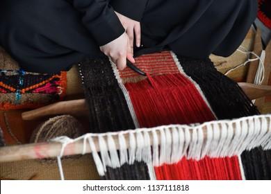 An Arab woman makes a traditional sadu weaving. Hands of a weaver close-up, focus on hands. Qatar