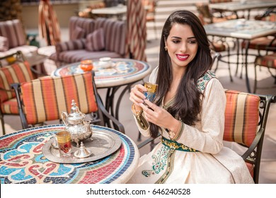 Arab Woman in national dress holding tea cup. Middle Eastern arab woman in traditional  Moroccan dress drinking Moroccan Tea. Ramadan holiday theme.