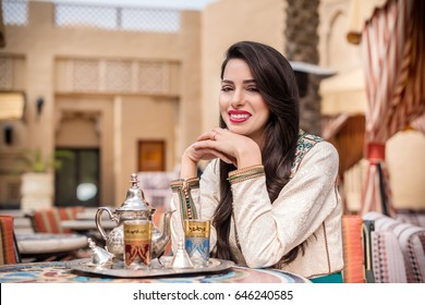 Arab Woman portrait. Middle Eastern arab woman in traditional  dress drinking Moroccan Tea and looking ithe camera. Ramadan holiday theme.