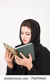 Arab woman praying and reading from the Holy Koran with white background