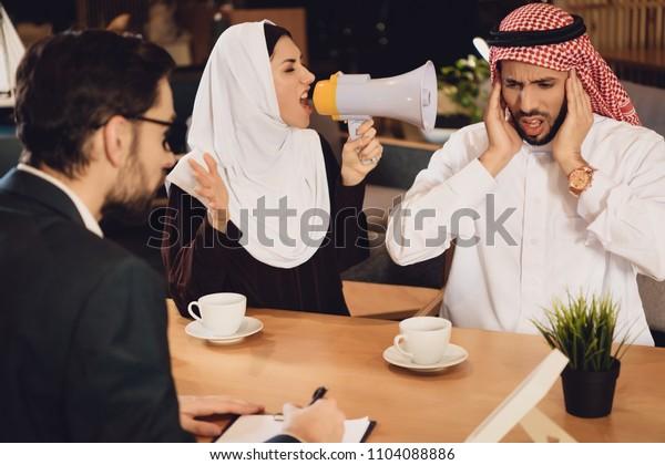 Arab woman at reception of psychotherapist screams into megaphone. Arab couple. Visit to psychotherapist.