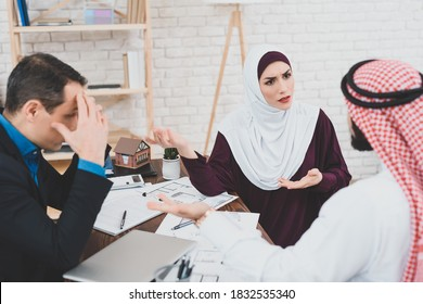 Arab woman sitting with men in office and arguing. A man and an Arab girl sit in the office of a realtor and argue about buying an apartment.