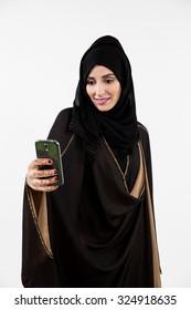 Arab woman taking selfie using mobile camera