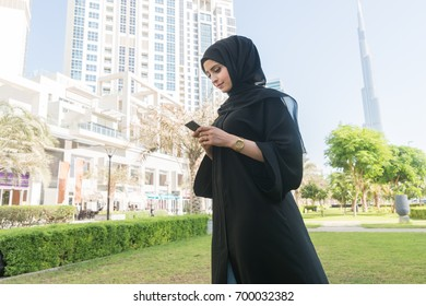 Arab woman typing messages using cell phone.