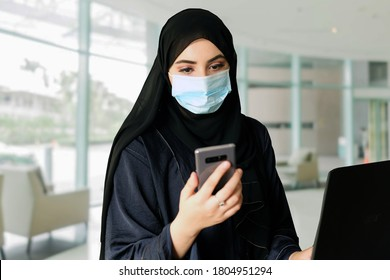 Arab woman wearing face mask while using mobile smart phone and practicing social distance at office. Emirati Arabic lady on traditional Hijab Abaya as part of Middle East culture